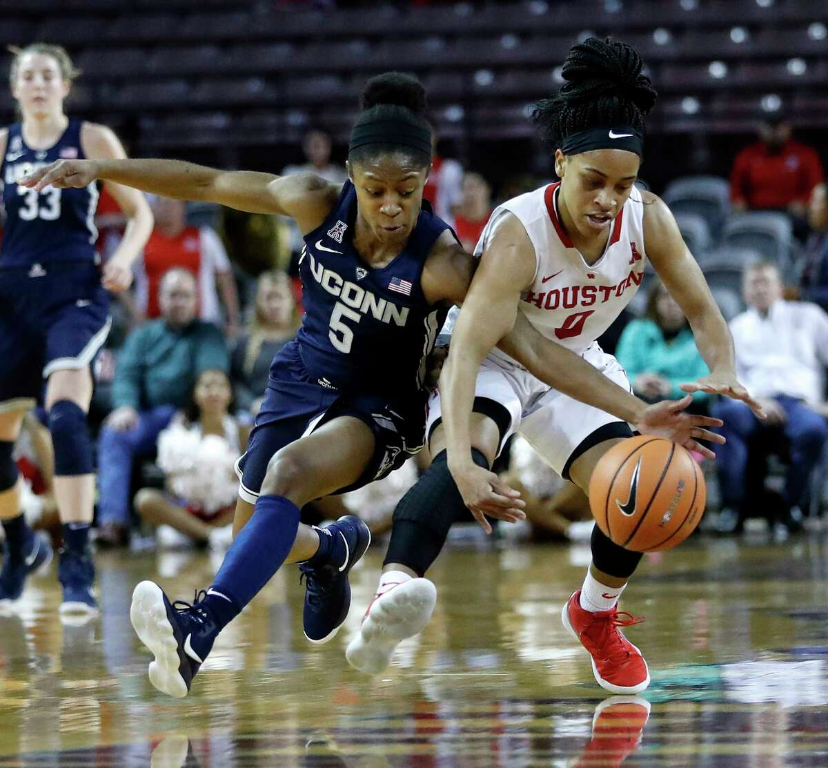 Connecticut Huskies guard Crystal Dangerfield (5) and Houston Cougars guard Angela Harris (0) both chase a loose ball during the first half of a NCAA basketball game at Texas Southern University Saturday, Jan. 13, 2018, in Houston.