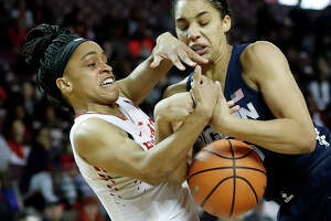 Houston Cougars guard Angela Harris (0) battles for control of the ball against Connecticut Huskies forward Gabby Williams (15) during the first half of a NCAA basketball game at Texas Southern University Saturday, Jan. 13, 2018, in Houston.