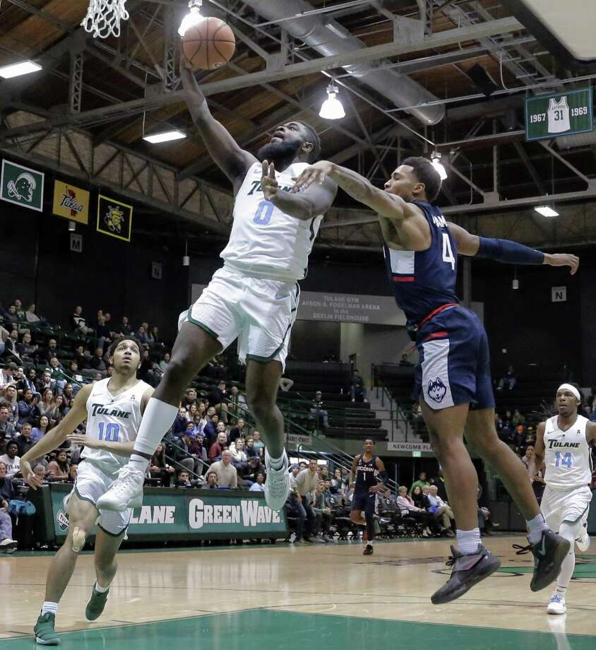 Tulane's Jordan Cornish (0) goes to the basket in front of UConn's Jalen Adams on Saturday in New Orleans. Photo: Brett Duke / Associated Press / NOLA.com The Times-Picayune