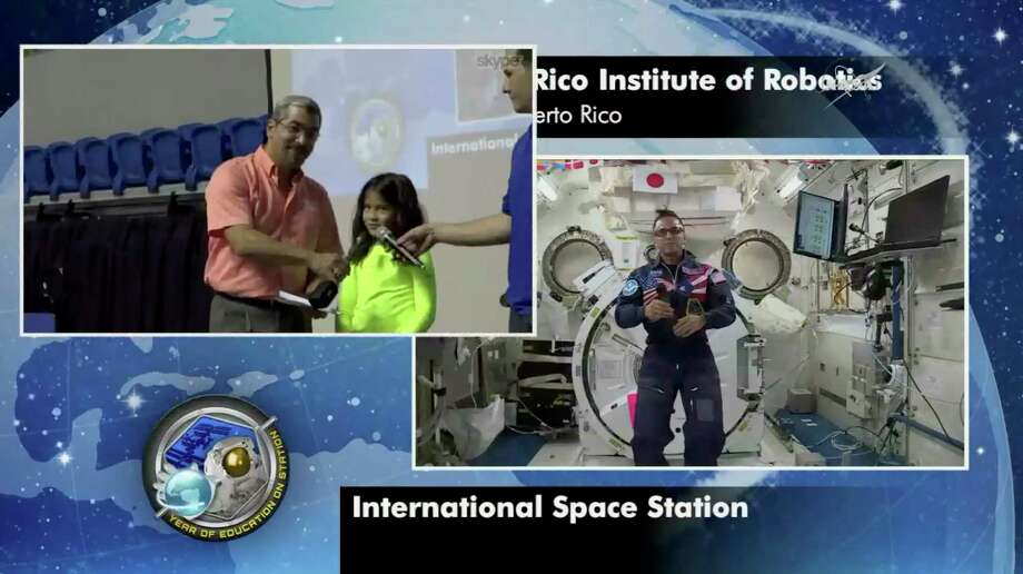 In this image from video made available by NASA, astronaut Joe Acaba, right, aboard the International Space Station, takes questions from students at the Puerto Rico Institute of Robotics in San Juan, Puerto Rico on Friday, Jan 12, 2018. One student asked how Puerto Rico looked from space after Hurricane Maria struck in September 2017. Acaba says the first thing he noticed was the lack of electricity, making the island almost impossible to see at night. (NASA via AP) Photo: HOGP / NASA