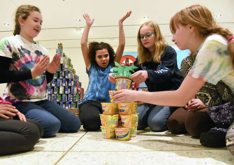 Troop 136 girl scout cadets, from left, Ashley Hogan, 11, Olivia Covington, 11, Lexi Slaski, 12, and Genevieve Glunk, 11, build a pineapple tree out of containers of cheese as Girl Scouts of Northeastern New York (GSNENY) participate in Girls CAN DO competition at the Empire State Plaza Concourse on Saturday, Jan. 13, 2018 in Albany, N.Y. Not seen in photo are Clare Duerr and Lilly Sweeney. (Lori Van Buren/Times Union) Photo: Lori Van Buren / 20042658A