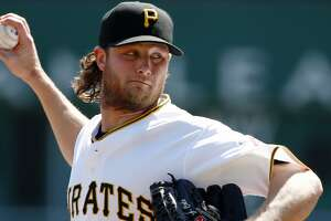 FILE - In this Sept 15, 2015, file photo, Pittsburgh Pirates starting pitcher Gerrit Cole warms up before a baseball against the Chicago Cubs in Pittsburgh. Pirates general manager Neal Huntington acknowledged a mistake was made in computing the young ace's salary and increased it to $541,000 for this year. But when Cole asked for more, he told the Pittsburgh Tribune-Review, the Pirates threatened to reduce his salary to the major league minimum, which states players with less than three years of service time must accept any salary at or over the minimum of $507,500.  (AP Photo/Gene J. Puskar, File)