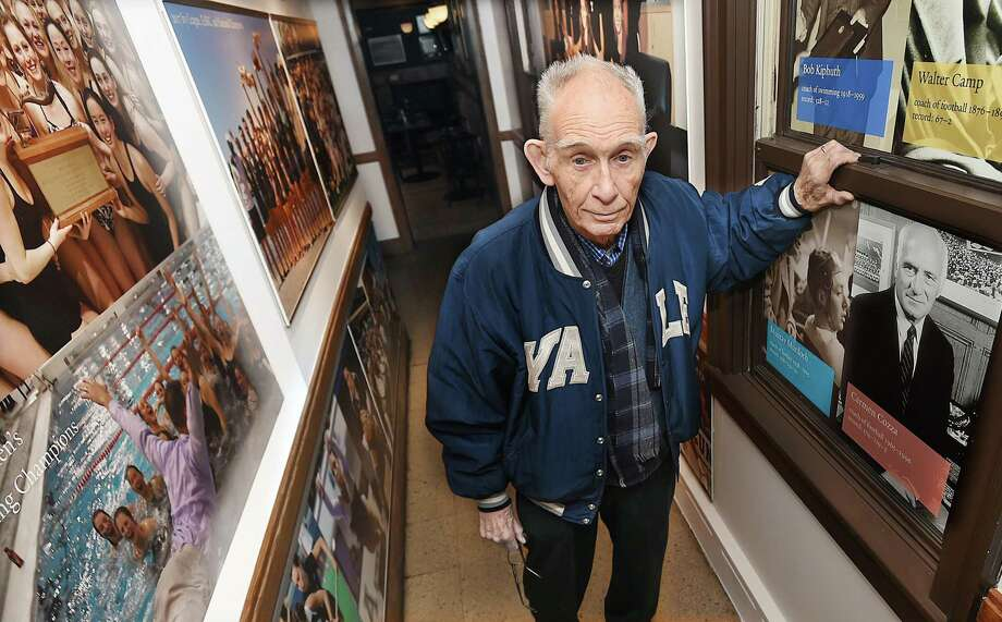 "Former New Haven Register editor and sports columnist Robert Barton near a photograph of the late Carmen ""Carm"" Cozza in the ""Hall of Champions"" at Mory's in New Haven. Photo: Catherine Avalone / Hearst Connecticut Media / New Haven Register"