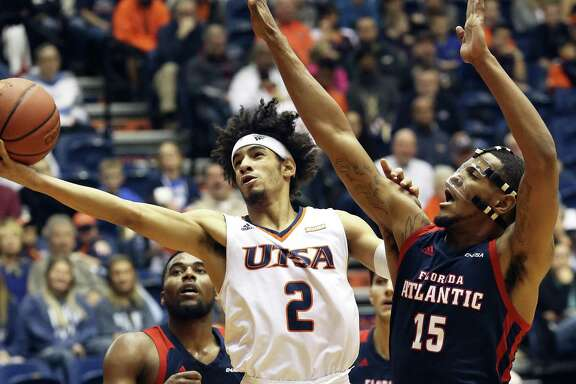 The Runner's Jhivvan Jackson stretches away from Jailyn Ingram to lay in a shot as UTSA hosts Florida Atlantic at the Convocation Center on January 13, 2018
