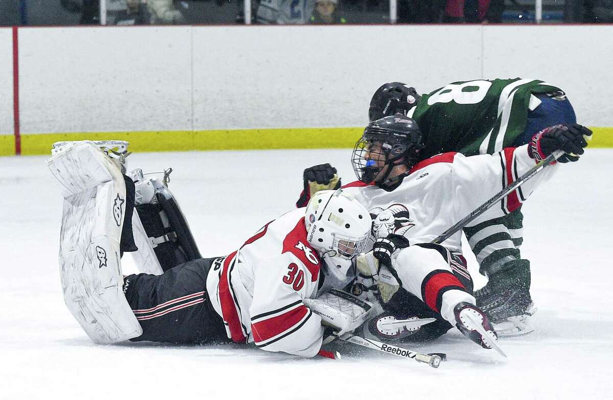 New Canaan goalie Dylan Shane collides with Shane Pickering and Northwest Catholic Nathan Loitz (8) in a boys hockey game at the Darien Ice House in Darien, Conn. on Saturday, Jan. 13, 2018. New Canaan defeated Northwest Catholic 3-1.