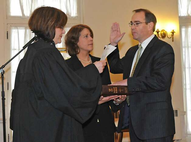 Schenectady County District Attorney Robert M. Carney takes oath of office officiated by Schenectady County Court Judge Karen Drago. Carney's wife Janine Kava holds a bible at the YWCA in Schenectady.  (Lori Van Buren / Times Union) Photo: LORI VAN BUREN