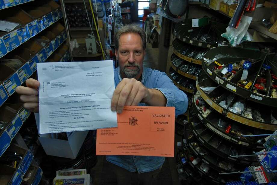 State paperwork, including a notice to pay a $50 fee, is displayed by Roy Jones, the manager of the Old Berne Mill hardware store manager in the Town of Berne. (Philip Kamrass / Times Union) Photo: PHILIP KAMRASS / 00005332A