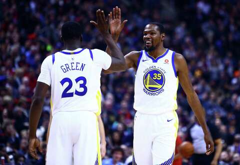 788d66bf2055 Kevin Durant  35 of the Golden State Warriors laughs and high fives  Draymond Green
