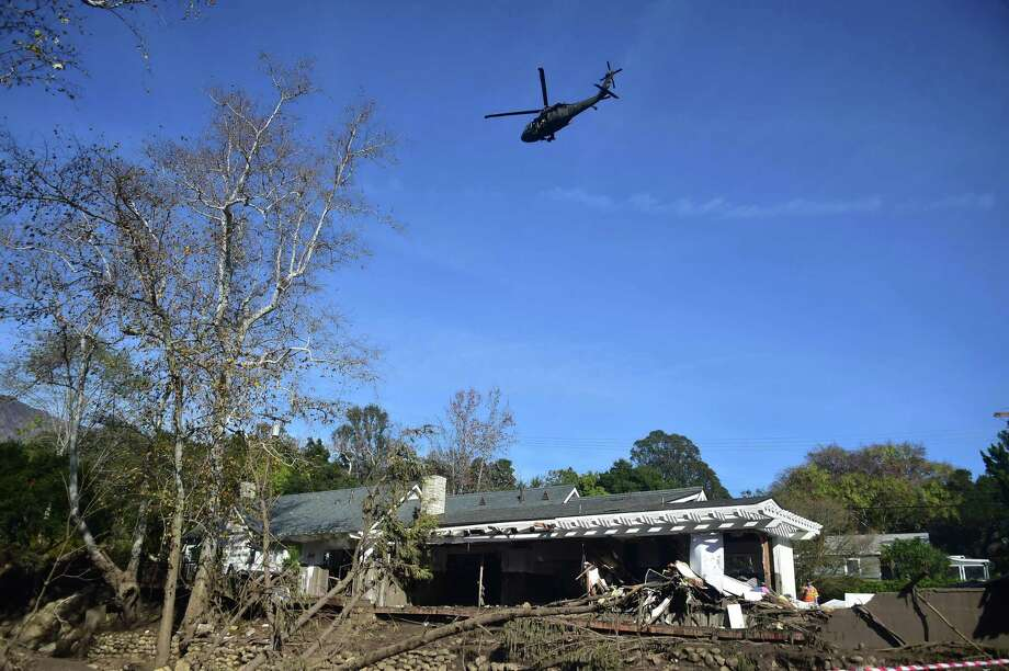 A helicopter flies over a home damaged in a mud slide in Montecito, California January 12, 2018. Heavy rains on January 9 sent rivers of waist-high mud and debris flowing from the hills into Montecito and other towns in Santa Barbara County northwest of Los Angeles, which are still recovering from last month's ferocious wildfires. At least 17 people died and dozens of residents are still unaccounted for. / AFP PHOTO / Frederic J. BROWNFREDERIC J. BROWN/AFP/Getty Images Photo: FREDERIC J. BROWN / AFP or licensors