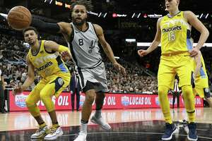 San Antonio Spurs' Patty Mills grabs for a loose ball between Denver NuggetsÕ Jamal Murray (left) and Nikola Jokic during first half action Saturday Jan. 13, 2018 at the AT&T Center.
