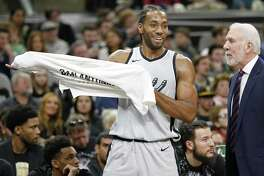 San Antonio Spurs' Kawhi Leonard jokes with head coach Gregg Popovich on the bench during first half action against the Denver Nuggets Saturday Jan. 13, 2018 at the AT&T Center.