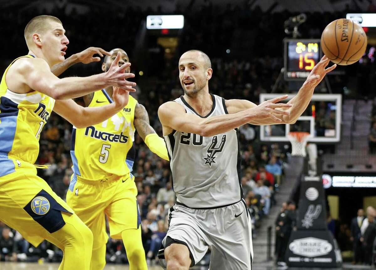 San Antonio Spurs' Manu Ginobili passes around Denver Nuggets?• Nikola Jokic (left) and Will Barton during first half action Saturday Jan. 13, 2018 at the AT&T Center.