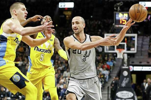 San Antonio Spurs' Manu Ginobili passes around Denver NuggetsÕ Nikola Jokic (left) and Will Barton during first half action Saturday Jan. 13, 2018 at the AT&T Center.