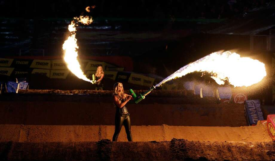 Monster Energy Girls wave flame throwers on the track during opening ceremonies of the Monster Energy Supercross held at NRG Stadium in Houston, TX, Jan. 13, 2018. (Michael Wyke / For the  Chronicle) Photo: Michael Wyke/For The Chronicle