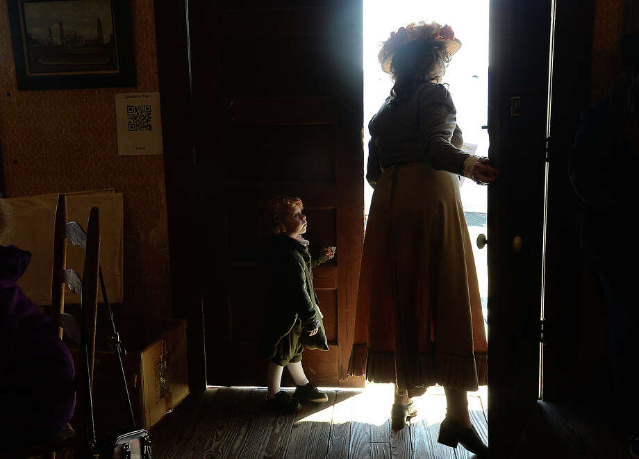 "Aidan Shajari watches as reenactor Sylvia Butler checks for any newcomers before starting her tea party demonstration in the saloon during the 117th anniversary celebration of the Spindletop Gusher at the Spindletop - Gladys City Boomtown Museum Saturday. Reenactors helped bring the spirit of the gusher era to life, and the buildings and craft activities, as well as a period fashion show, rounded out the festivities, along with the blowing of the ""gusher."" Photo taken Saturday, January 13, 2018 Kim Brent/The Enterprise Photo: Kim Brent / BEN"