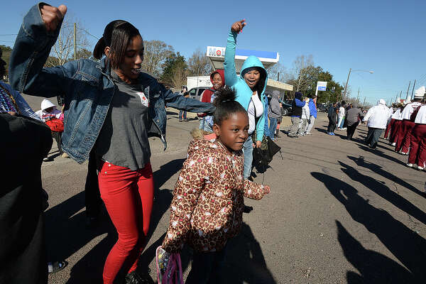 From left, Denise Citizen, Jakyra Citizen, and Marchelle Washington dance as Central High School's marching band performs during the annual MLK parade through South Park Saturday. Photo taken Saturday, January 13, 2018 Kim Brent/The Enterprise