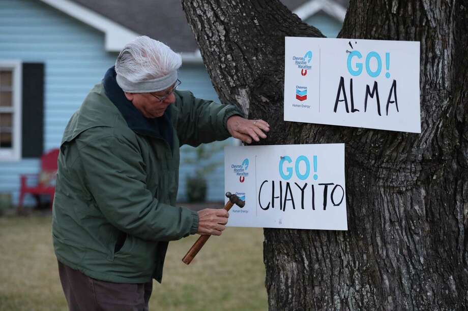 Gilbert Alvarez puts up signs for his daughter and niece as racer passes Edloe and University during the 2018 Chevron Houston Marathon Sunday, Jan. 14, 2014. Photo: Steve Gonzales / Houston Chronicle