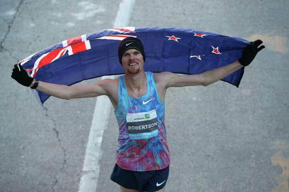 New Zealand runner Jake Robertson bears his national flag after winning the men's Aramco Half Marathon on Sunday, Jan. 14, 2018, in Houston. Photo: Yi-Chin Lee, Houston Chronicle / © 2018  Houston Chronicle