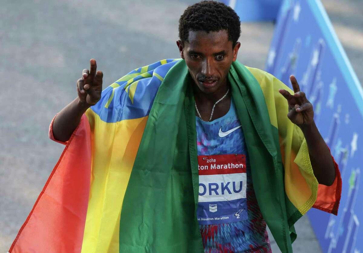 Ethiopian runner Bazu Worku bears his national flag after winning the Chevron Houston Marathon men's race on Sunday, Jan. 14, 2018, in Houston.