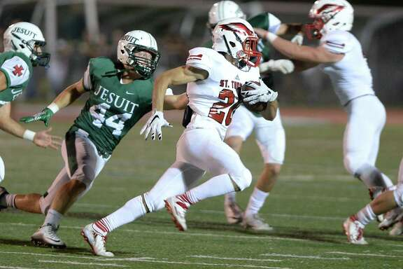 St. Thomas running back Brandon Hondros (20) turns up field past Michael Melody (44) of Strake Jesuit in the first quarter of a high school football game between St. Thomas and Strake Jesuit on September 2, 2016 at Crusader Stadium, Houston, TX.