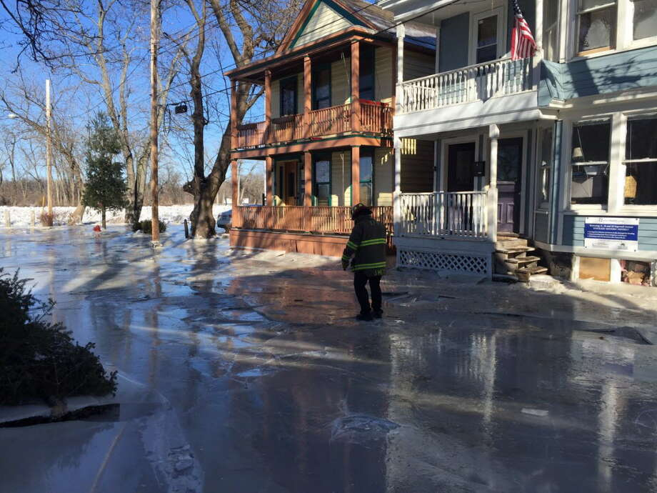 A Schenectady firefighter checks on residents after ice invaded streets in the Stockade neighborhood Jan. 14, 2018. (Steve Hughes/Times Union)