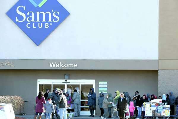 Shoppers stand in line outside of the entrance to Sam's Club in Orange on January 14, 2018.  The store is slated to close at the end of the month.