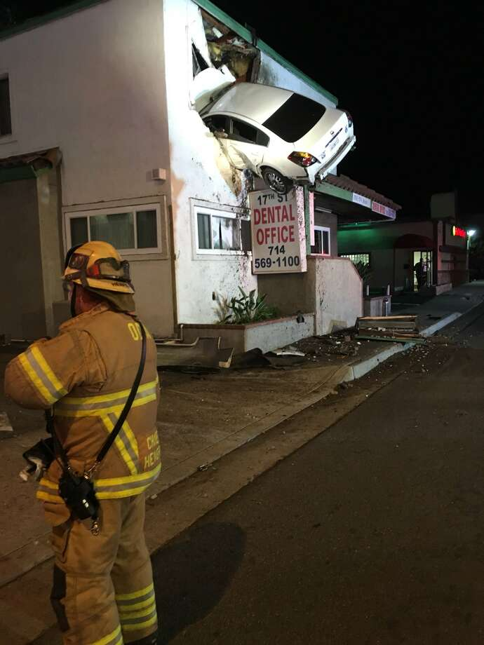 A vehicle crashed into the second floor of a small office building in Santa Ana, Calif. The vehicle hit the center divider and went airborne and landed into the building. One person self-extricated, the other person was still trapped in the vehicle. Photo: OCFA PIO