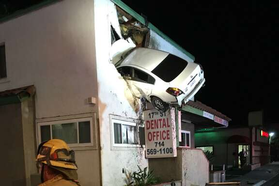 A vehicle crashed into the second floor of a small office building in Santa Ana, Calif. The vehicle hit the center divider and went airborne and landed into the building. One person self-extricated, the other person was still trapped in the vehicle.