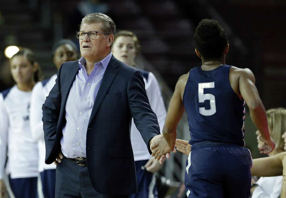 UConn head coach Geno Auriemma greets Crystal Dangerfield during Saturday's win over Houston.