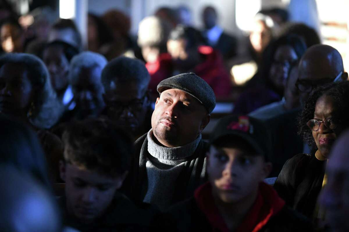 Manuel Rivera of New Haven (center) listens to a recording of the