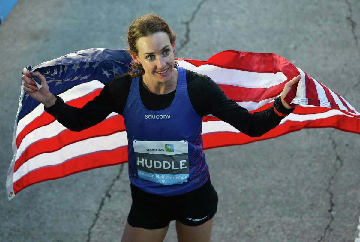 American runner Molly Huddle bears the American flag at the Aramco Half Marathon on Sunday, Jan. 14, 2018, in Houston. Huddle broke the U.S. women's half-marathon record with a record in 1:07:26. ( Yi-Chin Lee / Houston Chronicle )
