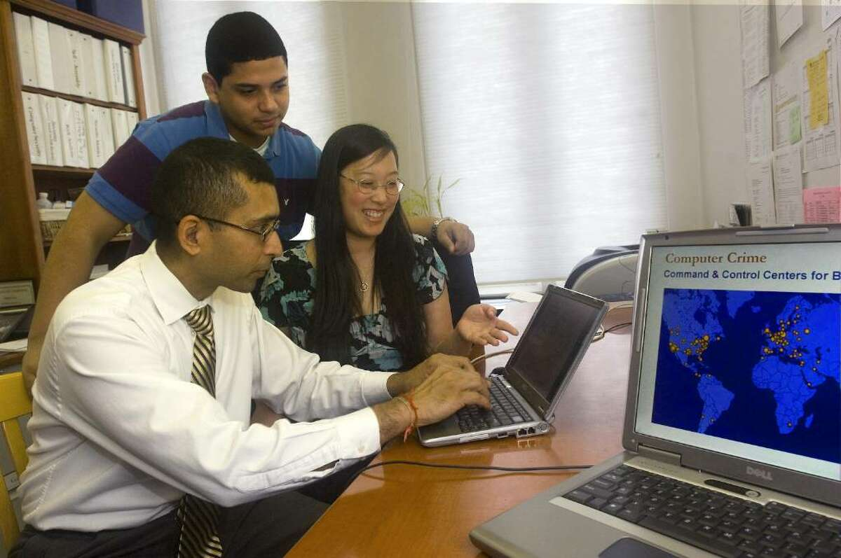Sanjay Goel, left, an associate professor at UAlbany, works against cyber attacks with UAlbany students Anthony Colon and Damira Pon. A Silicon Valley software company, Palantir Technologies of Palo Alto, has donated technology to UAlbany that will help the school conduct cybersecurity research and identify sources of cyberattacks. The software should allow researchers to combine information from a hacker forum with global network data to accurately predict the source of cyber attacks. (Courtesy UAlbany)