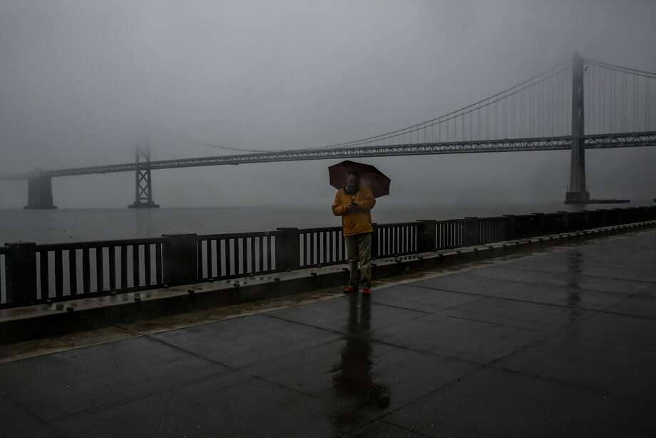 Two light storms are expected to make landfall in the Bay Area this week, forecasters said.  Roger E. pauses while walking on the Embarcadero during a rainstorm in San Francisco, Calif., on Monday, Jan. 8, 2018. Photo: Gabrielle Lurie, The Chronicle