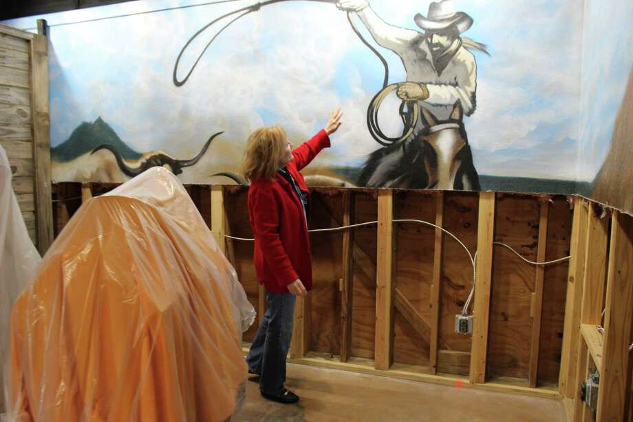 Butler Longhorn Museum director Monica Hughes shows a mural that was partially destroyed in August by flooding from Hurricane Harvey. The museum has been closed for repairs ever since. Photo: Yvette Orozco