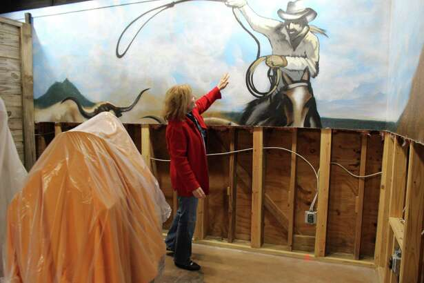 Butler Longhorn Museum director Monica Hughes shows a mural that was partially destroyed in August by flooding from Hurricane Harvey. The museum has been closed for repairs ever since.
