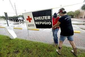 FILE - In this Aug. 25, 2017, file photo, volunteers set up signage outside the Civic Center, where the Red Cross set up a shelter for those who evacuated their homes due to storm damage in Beaumont, Texas. The American Red Cross will honor those who supported the Red Cross during the 2017 hurricanes with the 2018 Community Impact Award. These hurricane heroes will be honored at the Red Cross Heroes Ball on Saturday, March 3,at the Connecticut Convention Center in Hartford.