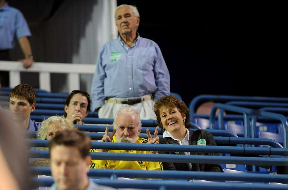 Bob Zuraw stretches his legs at the Pilot Pen tennis tournament in 2011. His daughter Cathy, Mike Daly and Sharon Daly, visible to the left, mug for Post photographer Christian Abraham. Photo: / Hearst Connecticut Media, Christian Abraham