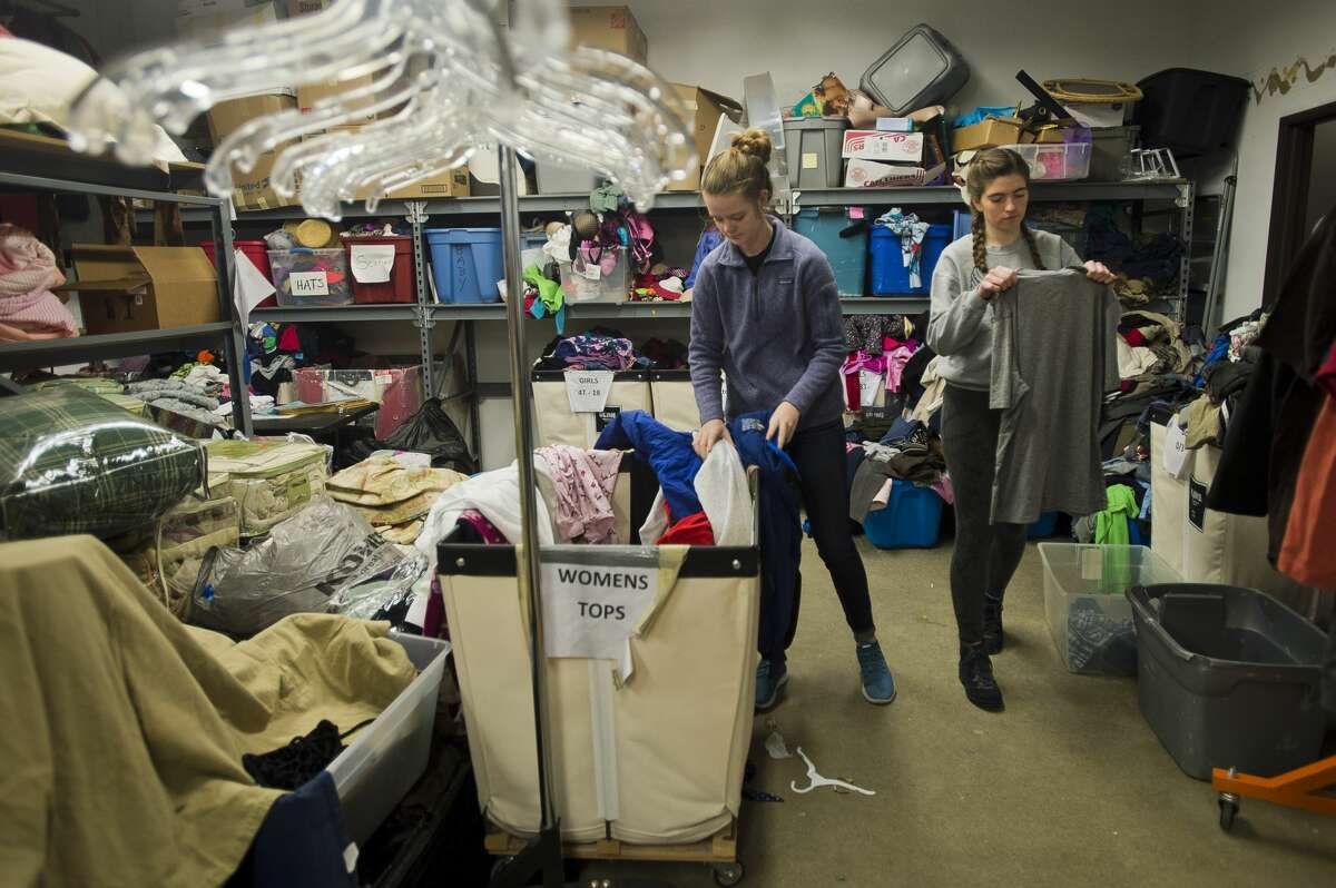 Midland High School seniors Madison Carroll, left, and Breanna Chritz, center, hang up articles of clothing during a day of volunteering at the Shelterhouse Resale Shop on Monday, Jan. 15, 2018 in honor of Martin Luther King, Jr. Day. (Katy Kildee/kkildee@mdn.net)