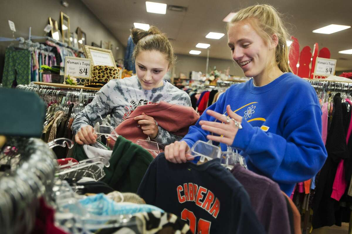Midland High School seniors Riley Rajewski, right, and Allison Gray, left, hang up articles of clothing during a day of volunteering at the Shelterhouse Resale Shop on Monday, Jan. 15, 2018 in honor of Martin Luther King, Jr. Day. (Katy Kildee/kkildee@mdn.net)
