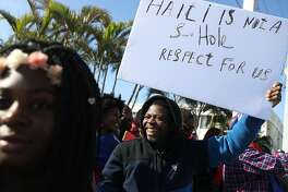 WEST PALM BEACH, FL - JANUARY 15:  (EDITORS NOTE: Caption contains profanity.) People join together, near the Mar-a-Lago resort where President Donald Trump spent the last few days,  to condemn President Trumps reported statement about immigrants from Haiti and to ask that he apologize to them on January 15, 2018 in West Palm Beach, Florida. President Trump is reported to have called Haiti, Africa and El Salvador places �shithole countries� last week, whose inhabitants are not desirable for U.S. immigration.  (Photo by Joe Raedle/Getty Images)
