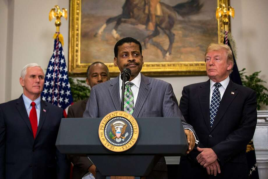 """President Donald Trump looks on as Isaac Newton Farris Jr., the nephew of Martin Luther King Jr., speaks during an event honoring King in the Roosevelt Room of the White House in Washington, Jan. 12, 2018. After the signing, Trump ignored a question from a reporter about whether he is a racist, a day after he reportedly referred to African countries as """"shitholes.""""  From right: Trump, Farris, Ben Carson, left, the secretary of Housing and Urban Development and Vice President Mike Pence. Photo: AL DRAGO, NYT"""