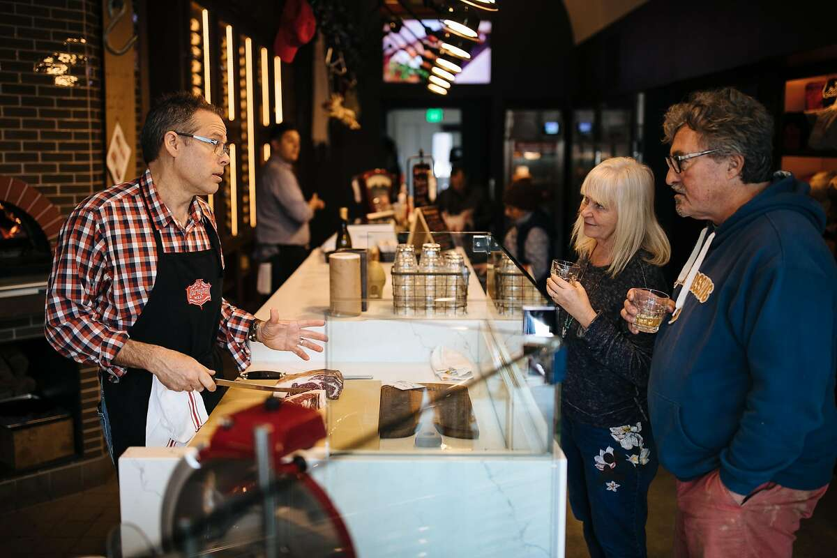 Pete Seghesio explains how to prepare their meats to his customers and friends, Kerry Damskey and Daisy Damskey, as they enjoy their wine tasting at the Journeyman Meat Co. in Healdsburg, Calif. Saturday, Jan. 13, 2018.