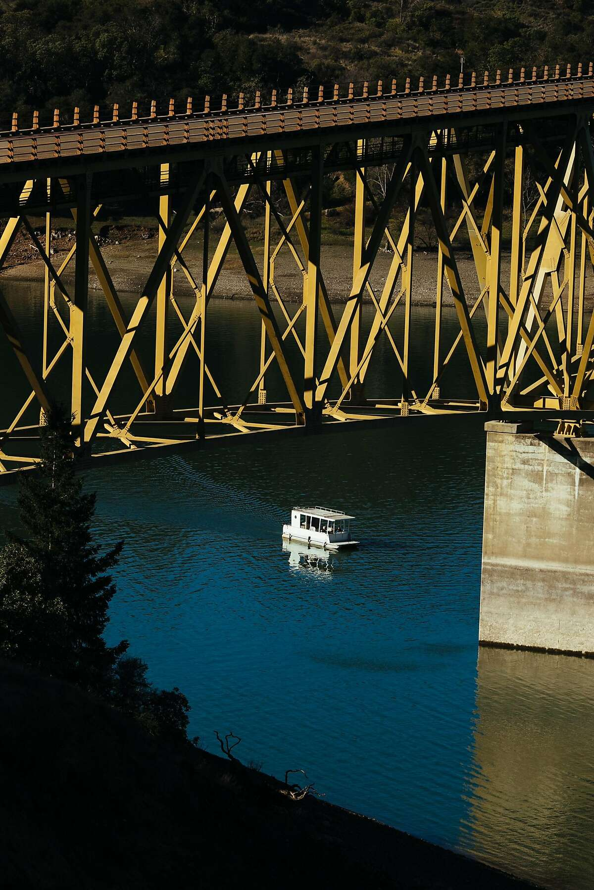 A boat makes its way under the Rockpile Road Bridge on Lake Sonoma in Geyserville, Calif. Saturday, Jan. 6, 2018.