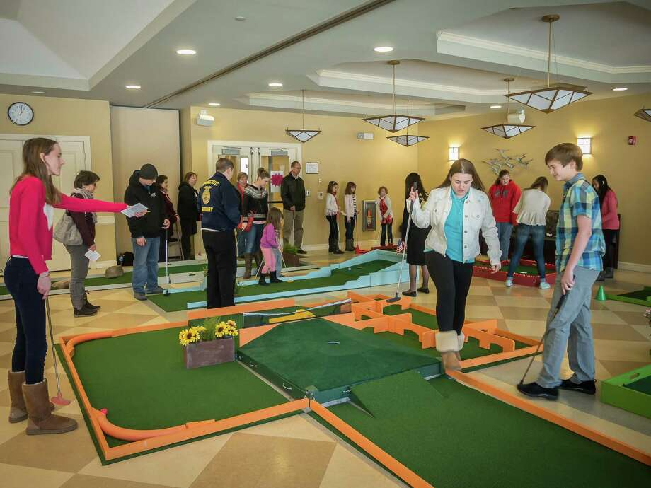 Families and friends at last year's event enjoy a round of indoor mini-golf at the Woodbury Senior Community Center. This year's fundraiser will be held on President's Day weekend, Feb. 16-19. Photo: Contributed Photo / ©2016 David Peter Arnold
