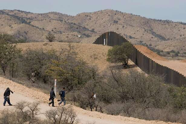 Migrants walk toward the U.S.-Mexico border wall on the outskirts of Nogales, Mexico, Tuesday, April 1, 2008. U.S. officials say the Bush administration will bypass more than 30 laws and regulations in an effort to complete 670 miles (1,050 kilometers) of fence along the U.S. border with Mexico by the end of this year. (AP Photo/Guillermo Arias)