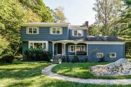 The blue colonial house at 15 Mail Coach Drive sits in Norwalk while the 1.19-acre level property on which it sits is in both Wilton and Norwalk.