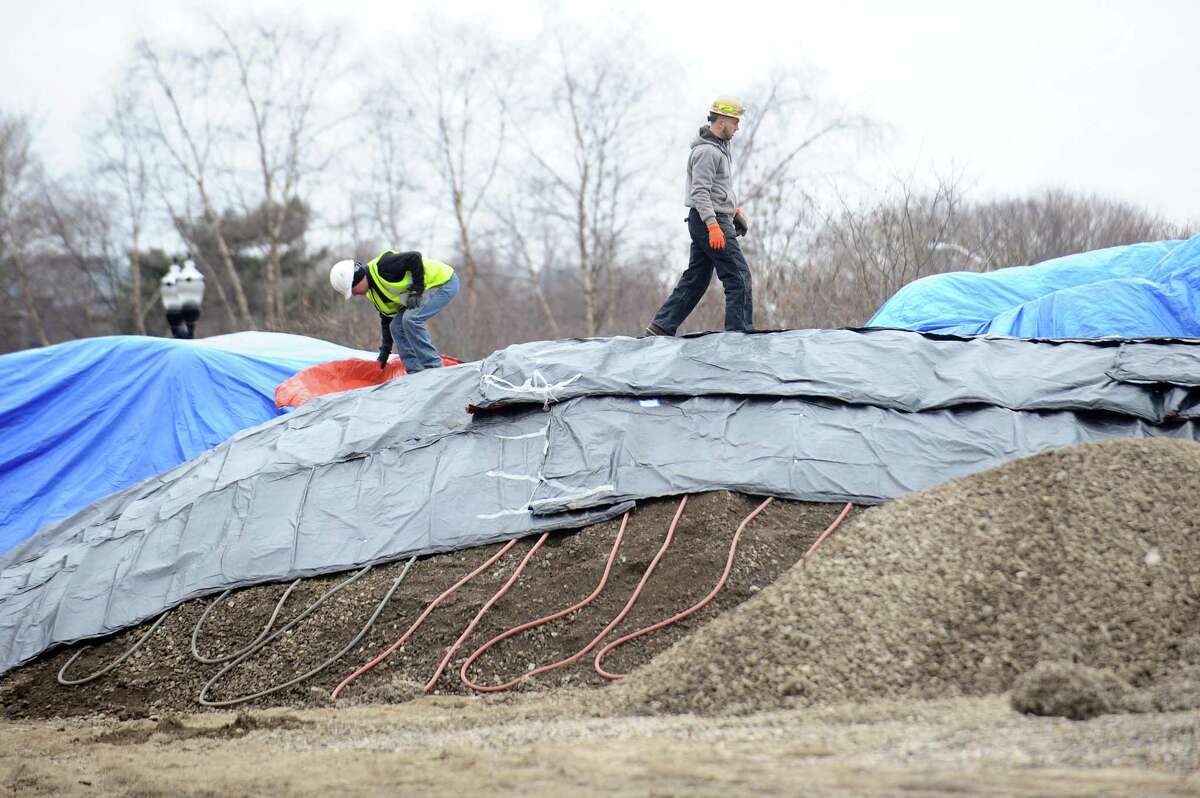Construction workers climb over a dirt pile at Mill River Park in downtown Stamford, Conn. on Sunday, Jan. 14, 2018. There will soon be a large fountain and skating rink installed in the park, the next step for the Mill River Collaborative after the carousel.