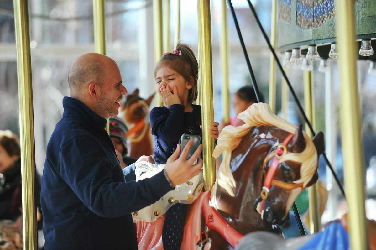 Three-year-old Ruby Tello shares a laugh with her father Craig while riding the Mill River Park Carousel in downtown Stamford, Conn. on Sunday, Jan. 14, 2018.