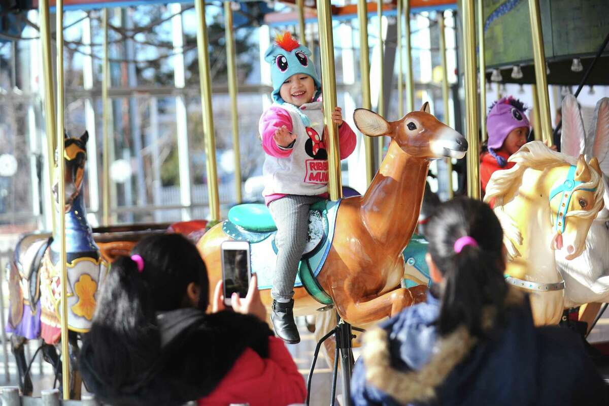 A young girl waves to her family while riding the Mill River Park Carousel in downtown Stamford, Conn. on Sunday, Jan. 14, 2018.