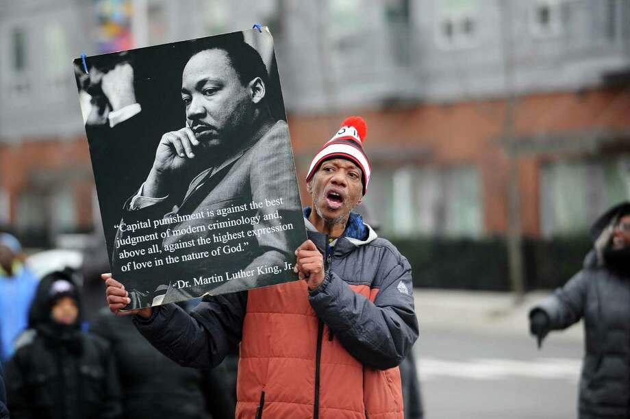 """Cornell Davis sings """"We Shall Not Be Moved"""" while holding up a quote from Dr. Martin Luther King Jr. while participating in the annual Martin Luther King Jr. Day march in Stamford, Conn. on Monday, Jan. 15, 2018. Photo: Michael Cummo / Hearst Connecticut Media / Stamford Advocate"""